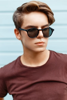 Closeup portrait of a handsome man with the hairstyle in sunglasses