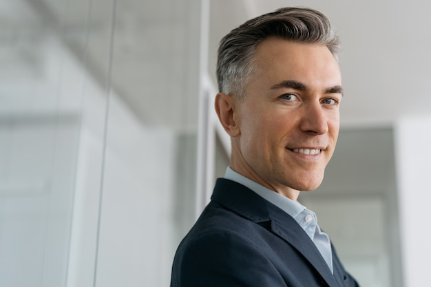 Closeup portrait of handsome mature businessman looking at camera in office. successful business