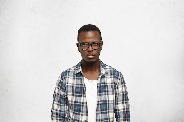 Ritratto del primo piano di giovane maschio nero bello, intelligente e sicuro di sé con l'espressione seria del viso