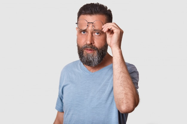 Closeup portrait of handsome young bearded man with glasses, wearing casual clothing, standing on white, raising his eyewear questioningly, doubts and.