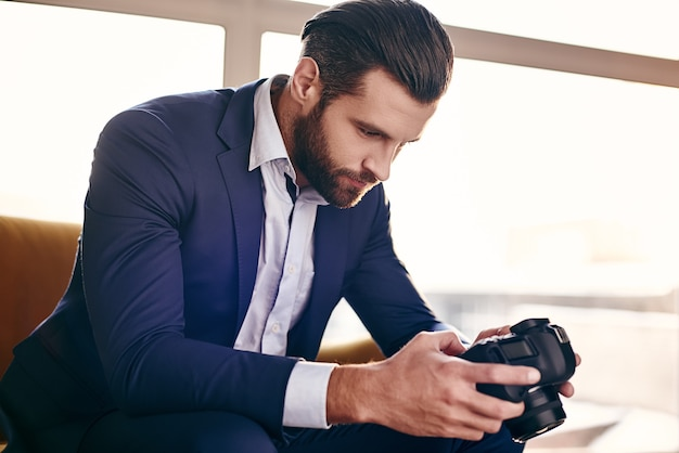 Closeup portrait of handsome young businessman in fashion suit who is looking at pictures on