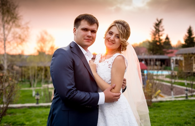 Closeup portrait of happy bride and groom hugging at sunset in park