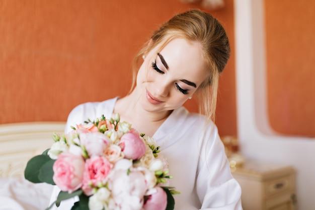 朝は白いバスローブでポートレート、幸せな花嫁をクローズアップ。彼女は花束を手で見て笑顔
