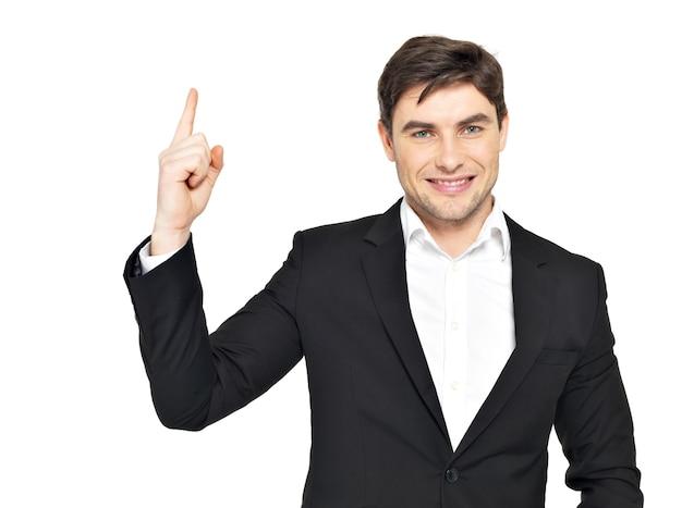 Il ritratto del primo piano dell'uomo d'affari felice punta il dito verso l'alto in abito nero isolato su bianco
