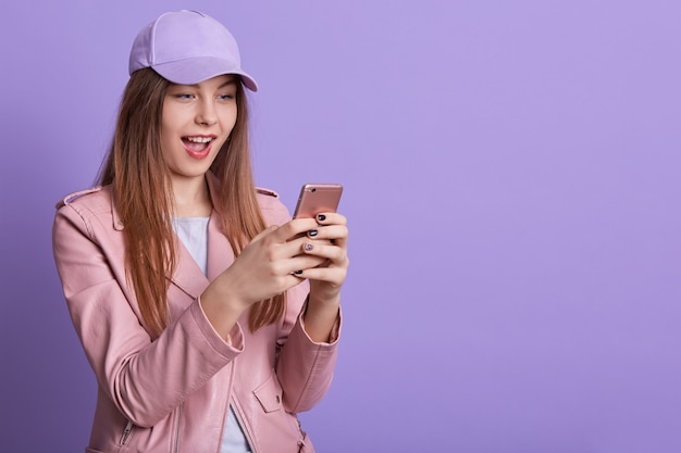Closeup portrait of happy girl with opened mouth, keeping modern smart phone in hands