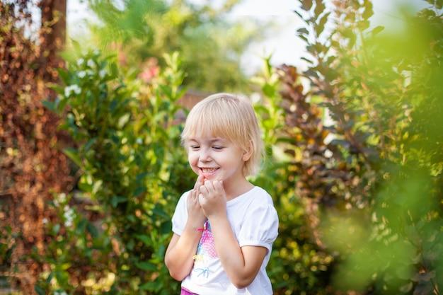 Closeup portrait of happy little blobde girl in elementary school age outdoors in green park