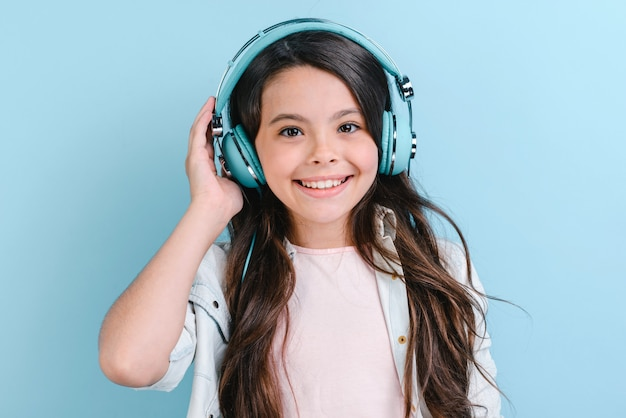 Closeup portrait of happy little girl in blue earphones listening to music and looking at the camera