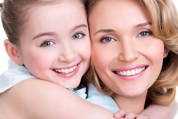 Closeup portrait of happy white mother and young daughter - isolated