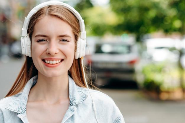 Closeup portrait of happy woman in earphones outdoor. blurring background