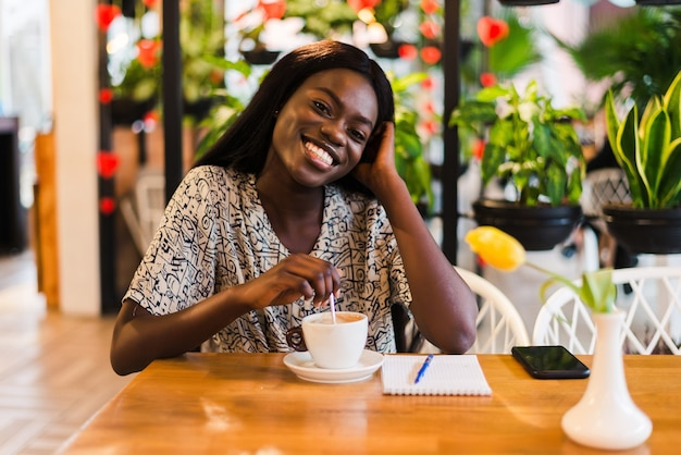 Closeup portrait of happy young black woman drinking coffee in cafe