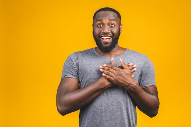 Closeup portrait of happy young handsome man looking shocked surprised open mouth eyes, isolated on yellow wall. positive human emotion facial expression feeling.