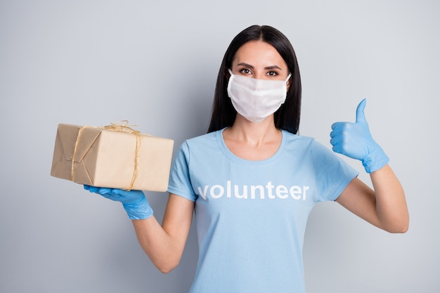 Closeup portrait of her she nice attractive girl voluntary worker holding on palm paper box charity social donation help showing thumbup isolated over grey pastel color background