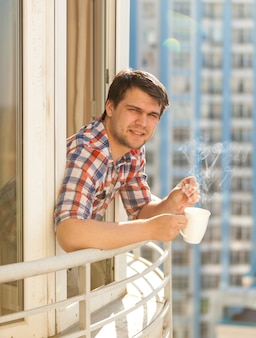 Closeup portrait of hipster guy drinking coffee on balcony