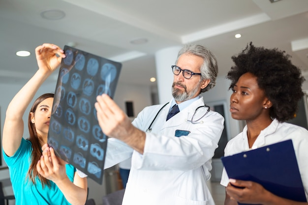 Closeup portrait of intellectual doctors healthcare personnel with white labcoat, looking at lungs x-ray radiographic image, ct scan, mri, isolated hospital clinic background. radiology department