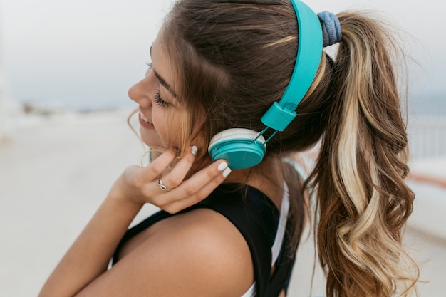海辺を歩いて長い巻き毛の青いヘッドフォンで音楽を聴くと、スポーツウェアのポートレートうれしそうな素晴らしい女性をクローズアップ。陽気な気分、外でのフィットネス、ファッショナブルなモデル