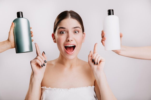 Closeup portrait of joyful girl posing without makeup on white wall. woman chose which shampoo is best to use.