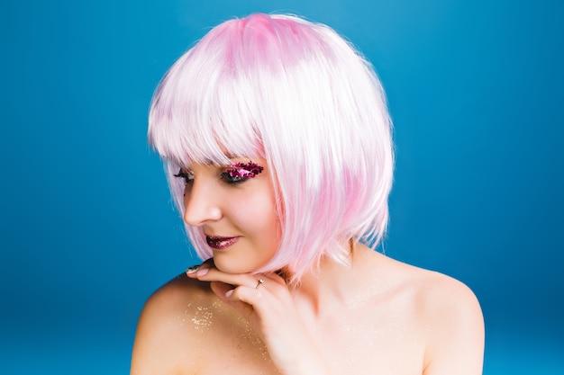 Closeup ritratto gioiosa giovane donna con spalle nude, taglio di capelli rosa sorridente a lato. trucco luminoso con orpelli rosa, carnevale sensibile, celebrativo, emozioni vere.