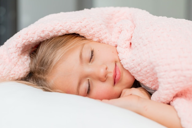 Closeup portrait of a little blonde girl lying and sleeping in a bed under a pink blanket