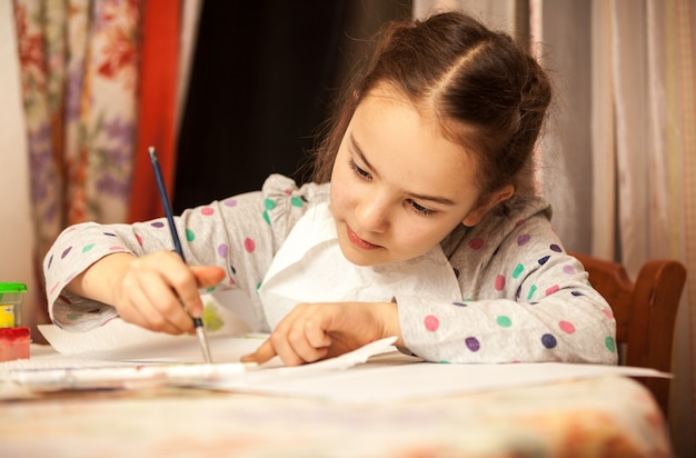 Closeup portrait of little girl drawing on canvas