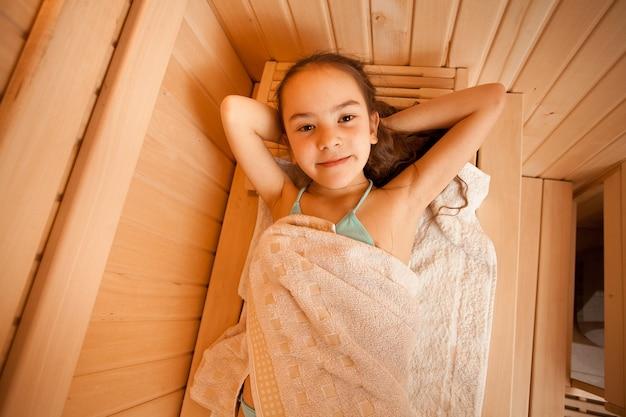 Closeup portrait of little girl lying at sauna
