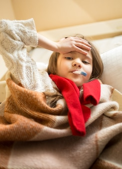 Closeup portrait of little girl in scarf lying in bed and measuring temperature