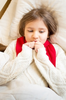 Closeup portrait of little girl in sweater ling in bed under blanket