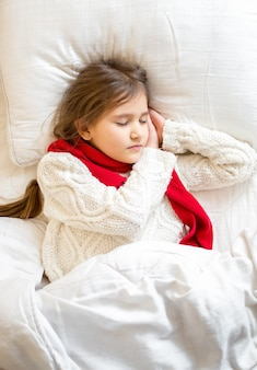 Closeup portrait of little girl in sweater sleeping at bed