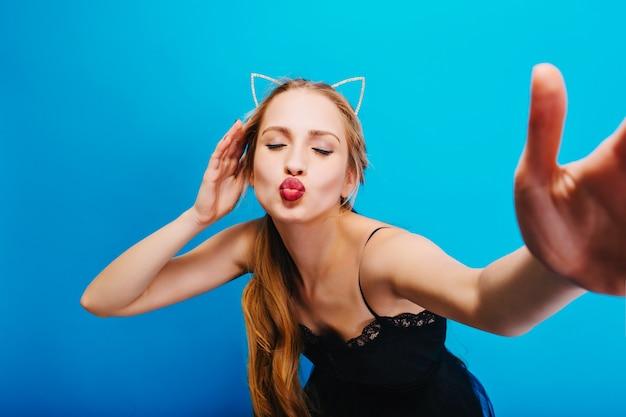 Ritratto del primo piano della ragazza adorabile che dà bacio, prendendo selfie, signora sulla festa. trucco luminoso con eyeliner. indossa un abito con pizzo, diadema di orecchie di gatto.
