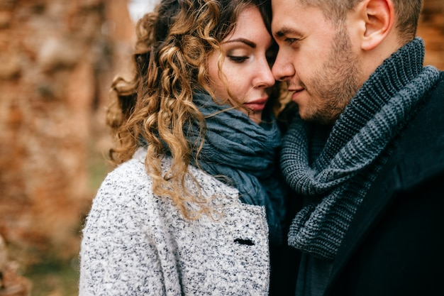 Closeup portrait of loving pair. two lovers outdoor standing cheek to cheek. man with woman hugs. tender, emotional, sensual girl and boy in love. male and female enjoying each other in castle ruins