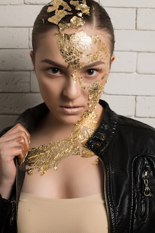 Closeup portrait of luxury brunette woman with gold foil on her face and neck, wearing leather jacket