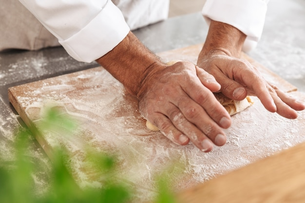 Closeup portrait of male hands making dough for bread, on table at bakery or kitchen