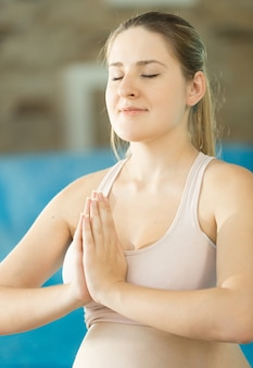 Closeup portrait of meditating young smiling woman