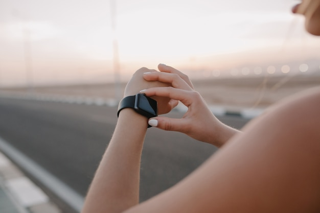 Closeup portrait modern watch on hands of sportswoman on road in sunny morning. workout, training, true emotions, healthy lifestyle, hardworking