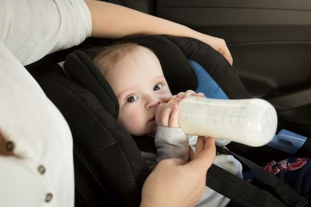 Closeup portrait of mother feeding baby in car from bottle