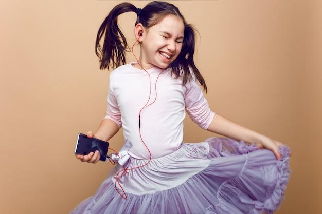 Портрет крупным планом забавы, маленькая девочка, слушающая, размышляя в наушниках, смеясь с закрытыми глазами