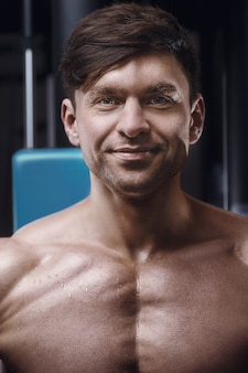 ジムでアスレチックハンサムな男のクローズアップの肖像画。ジムで6パックの筋肉質の胸と肩を持つ強力なボディービルダー。フィットネスとスポーツのコンセプト
