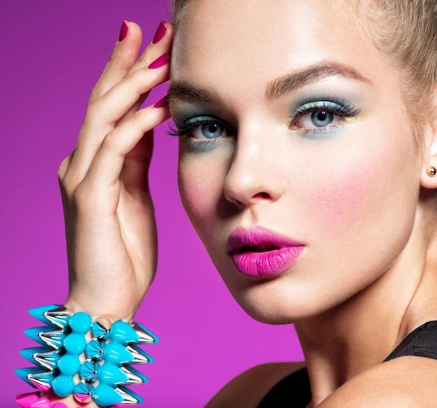 밝은 화장으로 아름 다운 패션 여자의 근접 촬영 초상화 매력적인 세련 된 소녀 핑크 벽의 화려한 글 래 머 소녀. 팔찌 가시와 여자의 초상화