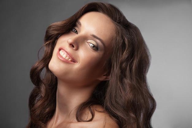 긴 곱슬 머리를 가진 행복한 생각을 하는 아름다운 젊은 여성의 클로즈업 초상화