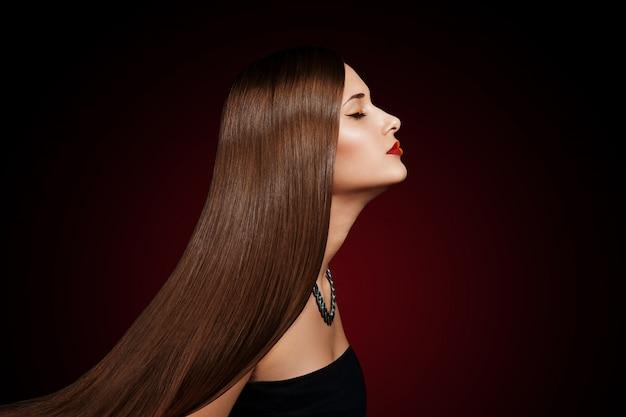 우아한 긴 빛나는 머리를 가진 아름 다운 젊은 여자의 근접 촬영 초상화