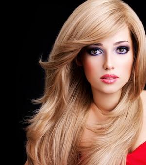 길고 흰 머리카락과 붉은 입술을 가진 아름 다운 젊은 여자의 근접 촬영 초상화. 검은 공간 위에 포즈를 취하는 패션 모델