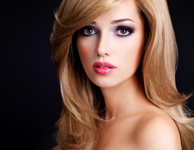 길고 흰 머리카락과 붉은 입술을 가진 아름 다운 젊은 여자의 근접 촬영 초상화. 검은 벽 위에 포즈 패션 모델