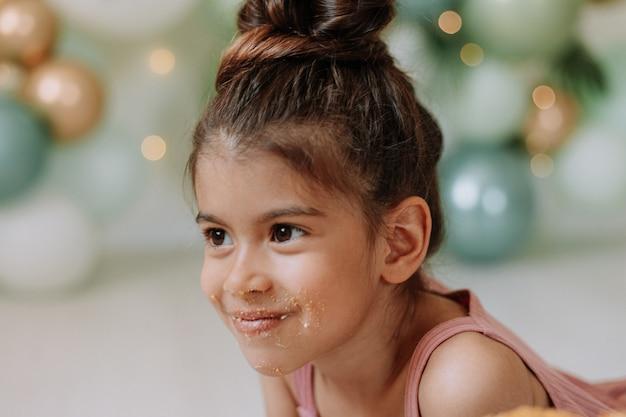 顔がケーキで汚れている茶色の目を持つブルネットの少女のクローズアップの肖像画ライフスタイル
