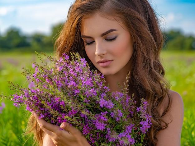 自然でリラックスした白人女性のクローズアップの肖像画。花束を持つ屋外の若い女性。彼女の手にラベンダーの花を持つフィールドの女の子。