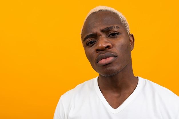 オレンジ色の魅力的な正直なハンサムな黒金髪アフリカ人のポートレート、クローズアップ