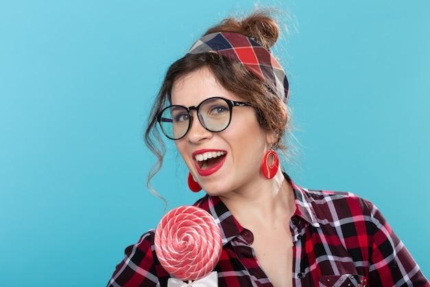 격자 무늬 셔츠와 안경에 매력적인 젊은 핀업 여자의 근접 촬영 초상화는 큰 핥는