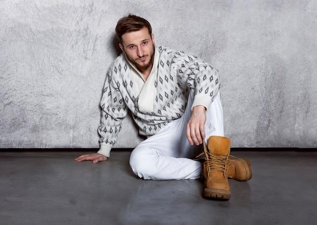 Крупным планом портрет уверенного в себе молодого человека в белых джинсах и кардигане, сидящего у стены