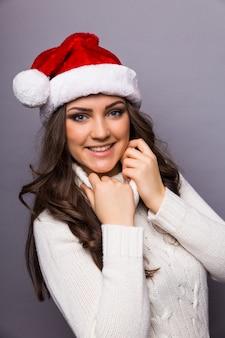Портрет крупного плана милой женщины рождества с красной шляпой санта-клауса, белым платьем, усмехаясь, счастливым, ожидая курортного сезона. положительные эмоции на изолированной серой стене.