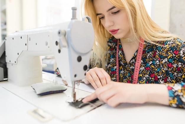 Портрет крупного плана милой молодой белошвейки сидя и шить на швейной машине.