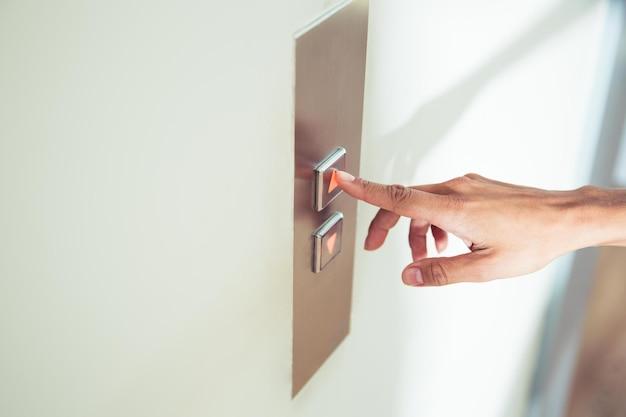 엘리베이터 버튼을 누르면 여성 손가락의 근접 촬영 초상화