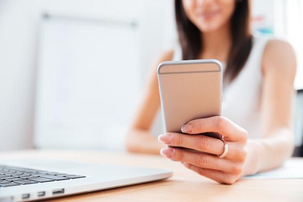 Крупным планом портрет женских рук с помощью смартфона в офисе
